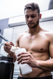 Muscular man making protein cocktail Royalty Free Stock Photography