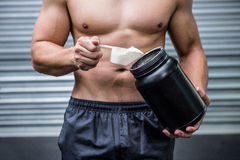 Muscular man making protein cocktail Royalty Free Stock Images