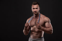 Muscular man with measurement tape Stock Images