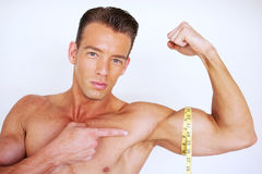 Muscular man measuring bicep Royalty Free Stock Image
