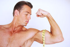 Muscular man measuring bicep Royalty Free Stock Images