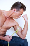 Muscular man measuring bicep Royalty Free Stock Photography