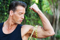 Muscular man measuring bicep Stock Photos