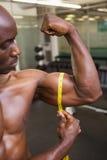 Muscular man measuring biceps in gym Stock Photo