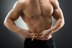 Muscular Man Measuring Fats With Caliper. Midsection of muscular man measuring fats with caliper against black background stock images