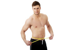 Muscular man measuring his belly. Stock Photography