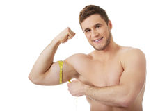Muscular man measuring his biceps. Stock Photo