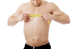 Muscular man measuring his chest. Stock Image