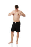 Muscular man measuring his chest. Stock Photography