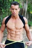 Muscular man measuring waist Royalty Free Stock Image