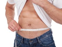 Muscular man measuring waist Royalty Free Stock Photography