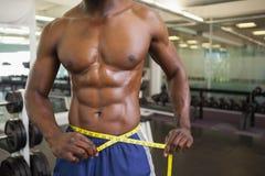 Muscular man measuring waist in gym Royalty Free Stock Photos