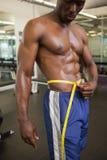 Muscular man measuring waist in gym Royalty Free Stock Image