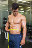Muscular man measuring waist in gym Stock Images