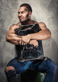 Muscular man with metal fuel can. Indoors Royalty Free Stock Photography