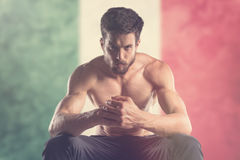 Muscular man with Mexico Flag behind. Muscular man royalty free stock photo