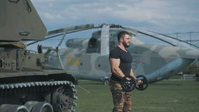 Muscular man in a military uniform has arranged training at a military base. The man is engaged with the bar, around military vehicles, tanks and helicopters stock video