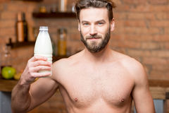 Muscular man with milk. Portrait of a naked muscular man holding a bottle with milk on the kitchen Royalty Free Stock Photo