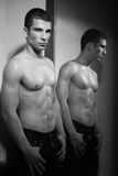 Muscular man and mirror Royalty Free Stock Photos
