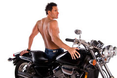 Muscular man and motorcycle. Back view of a sexy muscular man sitting on a motorcycle Royalty Free Stock Image