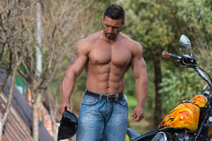 Muscular Man And Motorcycle royalty free stock images