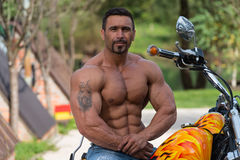Muscular Man And Motorcycle stock images