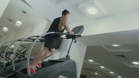 Muscular man moving up stairs training apparatus in gym. Muscular sportive man has a sport exercises in the gym. Handsome guy is moving up stairs and looks stock footage