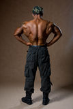 A muscular man with a naked torso in full view. His back Stock Photo