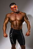 Muscular man with a naked torso. In the masquerade mask. Female seducer, a ladies' man in full growth on gray background Stock Images
