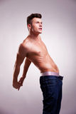 Muscular man with no shirt stretching Stock Images