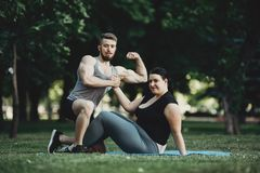 Muscular man and obese woman at street workout royalty free stock image