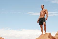 Muscular Man On Red Rocks Stock Photos