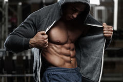 Muscular man with open jacket revealing abs in gym, working out Royalty Free Stock Image