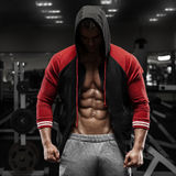 Muscular man with open jacket revealing abs in gym, workout. Shaped abdominal.  Royalty Free Stock Image