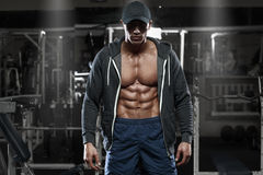 Muscular man with open jacket revealing chest and abs in gym, workout.  Stock Images