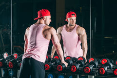 Muscular man out in gym standing near dumbbells,  a pink shirt and red baseball cap Stock Photo