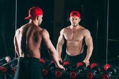 Muscular man out in gym standing near dumbbells , strong male naked torso abs Royalty Free Stock Photography