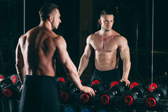 Muscular man out in gym standing near dumbbells , strong male naked torso abs Stock Image