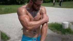 Muscular Man Outdoor Applying Oil to Skin stock footage