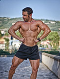 Muscular man outdoors in bodybuilding pose Royalty Free Stock Image