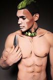 Muscular man with painted face and chest with dagger Royalty Free Stock Photo