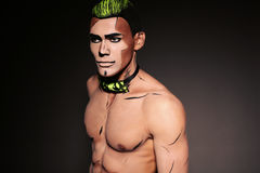 Muscular man with painted face and chest Royalty Free Stock Photo
