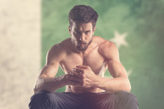Muscular man with Pakistan flag behind. Muscular man Royalty Free Stock Images