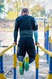 Muscular man on parallel bars stock images