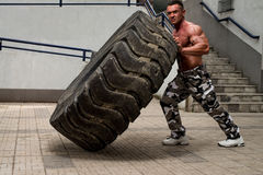 A muscular man participating in a cross fit workout by doing a tire flip Stock Image