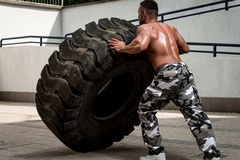 A muscular man participating in a cross fit workout by doing a tire flip Royalty Free Stock Images