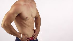 Muscular man with perfect abs flexing his muscles isolated. Cropped shot of a mid section of a shirtless athletic man showing off his six pack, copy space stock video