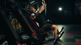 A muscular man performs exercises on pectoral muscles in a dark gym, lifting weights