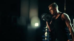 A muscular man performs exercises understands dumbbells for muscles of the biceps in a dark gym, lifting weights