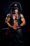 Muscular man in a pirate costume with a sword on a black backgro. Und stock photography